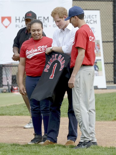 Britain's Prince Harry hits a baseball while participating in a baseball clinic in New York