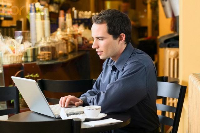 Businessman Working on Laptop in Coffee Shop