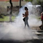 Demostrator walks near to tear gas fired by mlitary police at demostrators during protest against 2014 World Cup in Sao Paulo