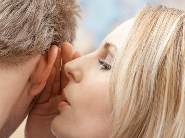 Woman whispering in man's ear