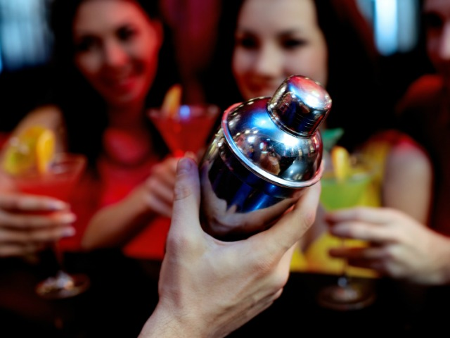 Close-up of male hand with shaker against people having fun at club