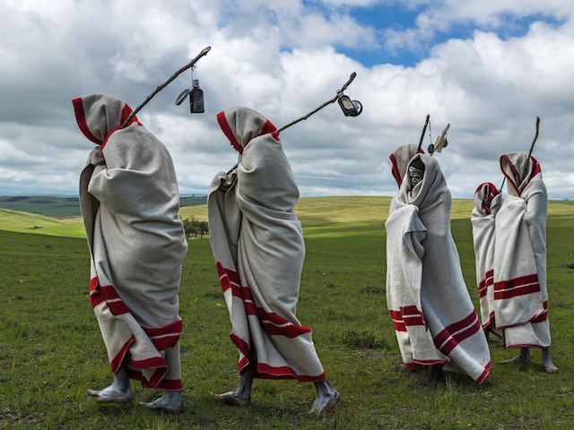 QUNU, EASTERN CAPE, SOUTH AFRICA, 14 DECEMBER 2013: Xhosa Initiates pass by close to the funeral of Nelson Mandela, Qunu, South Africa, 14 December 2014. These initiates have recently been circumsized traditionally and without anesthetic. They will spend up to two months dressed this way and learning the tradtions of Xhosa culture. Nelson Mandela, an icon of democracy, also went through this tradtional ritual. Mandela was buried at his family home in Qunu after passing away on the 5th December 2013.