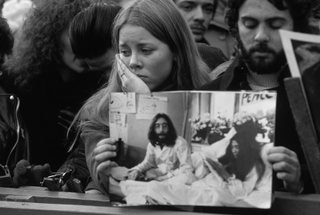 December 1980: A man and woman among the crowd in Central Park, New York, who have gathered to mourn the death of John Lennon. The man holds a picture of Lennon and Yoko Ono in bed during one of their 'love-in' peace protests. (Photo by Luiz Alberto/Keystone/Getty Images)