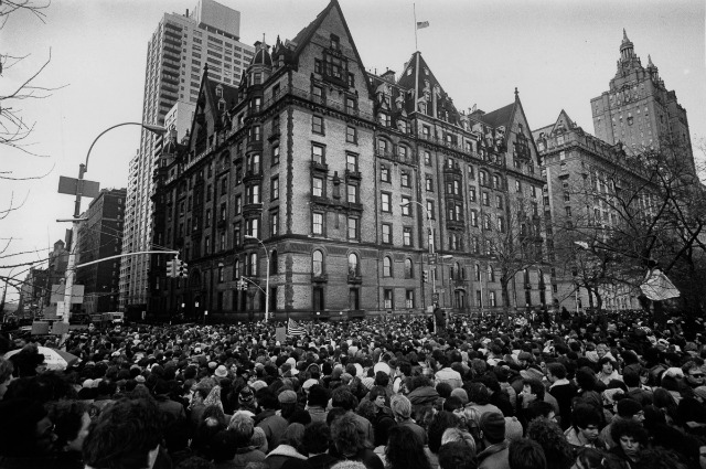 December 1980: Crowds gathering outside the home of John Lennon in New York after the news that he had been shot and killed. A flag flies at half-mast over the building. (Photo by Keystone/Getty Images)