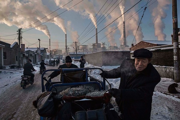 Daily life, first prize, singles - Kevin Frayer Chinese men pull a tricycle in a neighborhood next to a coal-fired power plant in Shanxi, China Photograph: Kevin Frayer/Getty Images/World Press Photo 2016