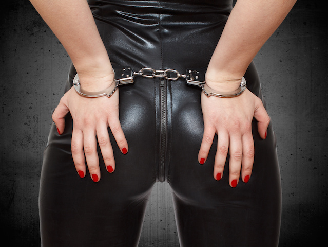 Sexy dominatrix, hands on ass in handcuffs, closeup