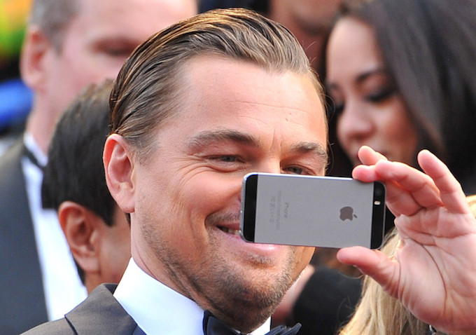 Leonardo DiCaprio uses his cell phone as he arrives at the Oscars on Sunday, March 2, 2014, at the Dolby Theatre in Los Angeles.  (Photo by Vince Bucci/Invision/AP)