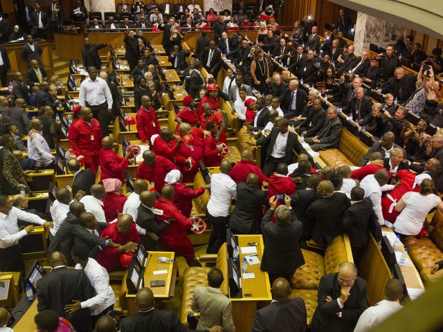 South African Economic Freedom Fighters, EFF,  disrupt the official opening session inside Parliament as Security personnel, dressed in white shirts, try and stop the violence in Cape Town, South Africa, Thursday, Feb. 12, 2015.  Security guards entered South Africa's parliament on Thursday to remove opposition lawmakers who disrupted an annual address by President Jacob Zuma to demand that he answer questions about a spending scandal.   (AP Photo/Rodger Bosch, Pool) 20final