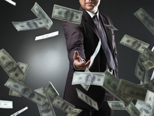 Handsome young man throwing money over dark background