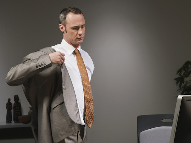 Businessman in office putting on jacket