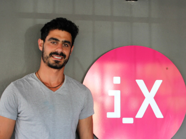 iX-founder-Aaron-infront-of-logo