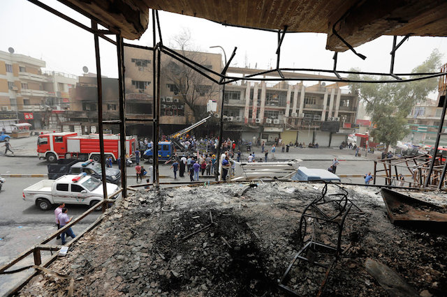 People gather at the site after a suicide car bomb attack at the shopping area of Karrada, a largely Shi'ite district, in Baghdad, Iraq July 4, 2016. REUTERS/Ahmed Saad