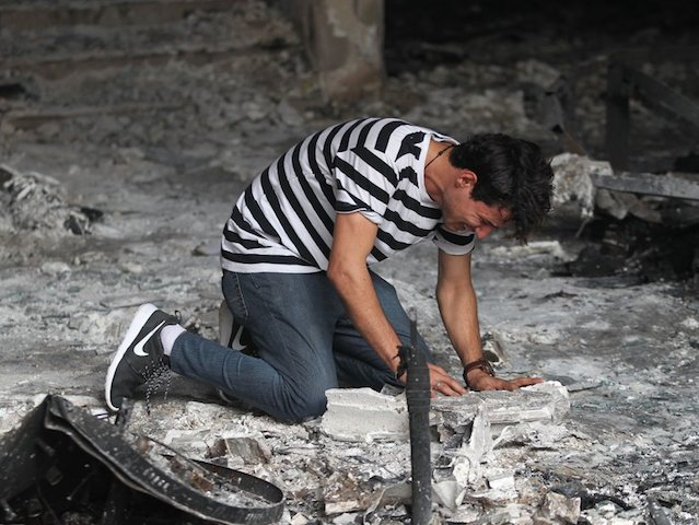 TOPSHOT - An Iraqi man reacts on July 4, 2016 as he enters a building that was destroyed in a suicide-bombing attack which took place a day earlier in Baghdad's Karrada neighbourhood. Iraqis mourned the more than 200 people killed by a jihadist-claimed suicide car bombing that was among the deadliest ever attacks in the country. The blast, which the Islamic State group said it carried out, hit the Karrada district early on July 3 as the area was packed with shoppers ahead of this week's holiday marking the end of the Muslim fasting month of Ramadan. / AFP / AHMAD AL-RUBAYE        (Photo credit should read AHMAD AL-RUBAYE/AFP/Getty Images)