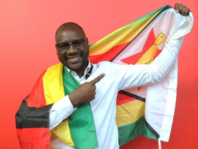 This photo taken Tuesday May 3, 2016 shows Evans Mawarire, a young pastor, posing with a Zimbabwean flag wrapped around his body, in Harare. Mawarire launched  the #Thisflag campaign to protest alleged government failures. (AP Photo/Tsvangirayi Mukwazhi)