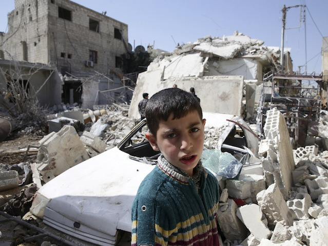 A boy looks on while residents inspect a damaged building in the rebel held besieged city of Douma, a suburb of Damascus, Syria February 27, 2016. REUTERS/Bassam Khabieh - RTS89AQ
