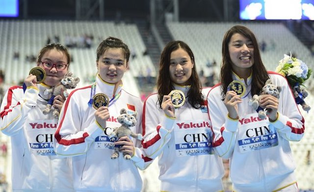 Team China celebrates its gold medal during the podium ceremony for the women's 4x100m medley relay swimming event at the 2015 FINA World Championships in Kazan on August 9, 2015. Shi Jinglin, Lu Ying, Fu YuanHui and Shen Duo competed in the event. AFP PHOTO / MARTIN BUREAU (Photo credit should read MARTIN BUREAU/AFP/Getty Images)