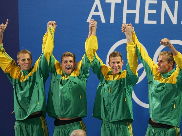 ATHENS - AUGUST 15:  Gold medalists Darian Townsend, Lyndon Ferns, Mark Roland Schoeman and Ryk Neethling of South Africa stand on the podium during the men's swimming 4 x 100 metre freestyle relay medal event on August 15, 2004 during the Athens 2004 Summer Olympic Games at the Main Pool of the Olympic Sports Complex Aquatic Centre in Athens, Greece. Michael Phelps (R) lost his million dollar contract offered by Speedo if he won seven Olympic gold medals after the American team lost to the South African's. (Photo by Adam Pretty/Getty Images) *** Local Caption *** Darian Townsend;Lyndon Ferns;Mark Roland Schoeman;Michael Phelps