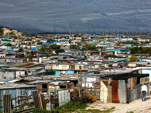 Residents walk through shacks in Cape Town's crime-ridden Khayelitsha township in this picture taken July 9, 2012. At least 11 people have died at the hands of vigilantes in the township since January as angry residents, tired of poor policing, take the law into their own hands. Picture taken July 9, 2012. To match Feature SAFRICA-CRIME/    REUTERS/Mike Hutchings (SOUTH AFRICA - Tags: CRIME LAW) - RTR34VCV