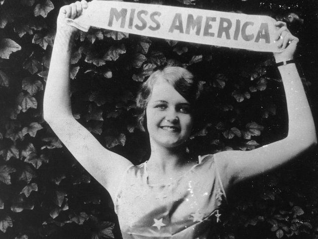 1927:  Miss America Lois Delander of Joliet, Illinois, holds up her title sash and wears a star print top, celebrating her victory. She served the longest time of any Miss America winner, as the pageant did not resume until 1933.  (Photo by Hulton Archive/Getty Images)