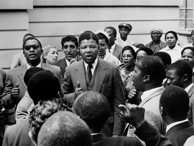 Black S. African atty. Nelson Mandela (C) w. wife Winnie (C) behind him) in midst of co-defendants acquitted (1957 charge) in treason trial.