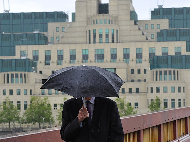 A man shields himself from the rain as he walks near the MI6 building in London August 25, 2010. A man who worked for the Secret Intelligence Service MI6 had been found murdered at a flat near the agency's headquarters, local media said on Wednesday. Police said they found the body of a man aged 30s, in the top floor of a flat at the upmarket Pimlico area of London on Monday afternoon. REUTERS/Toby Melville (BRITAIN - Tags: CRIME LAW) - RTR2HJ5K