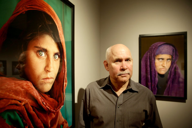 "US photographer Steve McCurry poses next to his photos of the ""Afghan Girl"" named Sharbat Gula at the opening of the ""Overwhelmed by Life"" exhibition of his work at the Museum for Art and Trade in Hamburg, northern Germany on June 27, 2013. The exhibition comprises some 120 photographs taken between 1980 and 2012 in countries such as Afghanistan, the United States, Pakistan, India, Tibet, Kashmir, Cambodia, Indonesia, Burma and Kuwait. AFP PHOTO / DPA / ULRICH PERREY GERMANY OUT RESTRICTED TO EDITORIAL USE, MANDATORY MENTION OF THE ARTIST UPON PUBLICATION, TO ILLUSTRATE THE EVENT AS SPECIFIED IN THE CAPTION (Photo credit should read ULRICH PERREY/AFP/Getty Images)"